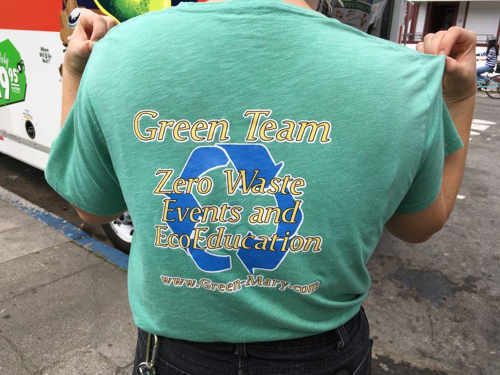 Voluntário de costas mostra camiseta com a frase Green Team